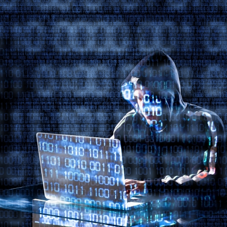 data theft: Hacker typing on a laptop with binary code in background