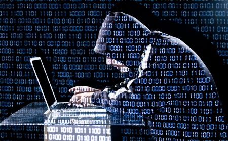 cyber crime: Hacker typing on a laptop with binary code in background