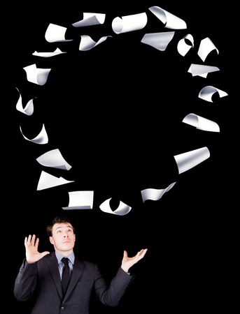 manipulating: Businessman manipulating sheets of paper isolated on black background