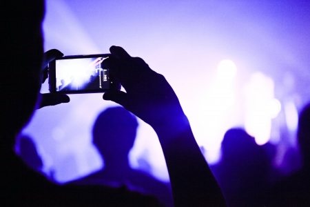 taking photograph: Someone talking a picture during a concert with a phone