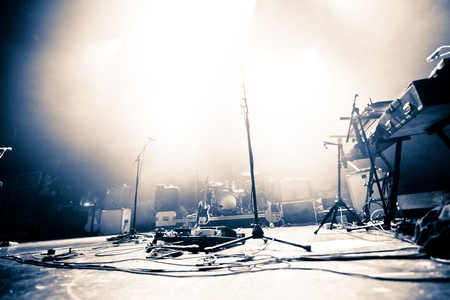 Empty illuminated stage with drumkit, guitar and microphones photo