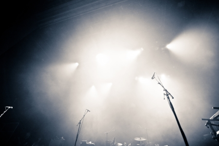 concert stage: Empty illuminated stage with drumkit, guitar and microphones Stock Photo