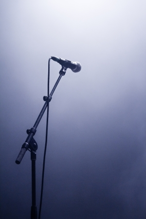 microphone stand: Microphone waiting for a voice in silhouette on a stage Stock Photo