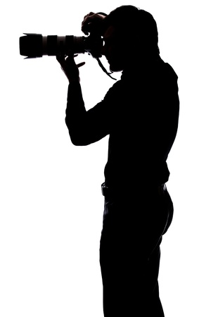 Professional photographer taking a picture in silhouette isolated over white background