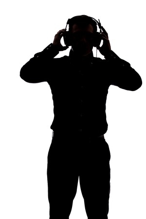 Man listening to music with headphones in silhouette isolated over white background