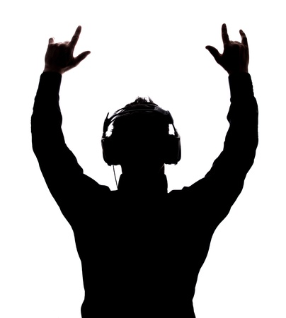 listening back: Man rocking on with headphones in silhouette isolated over white background