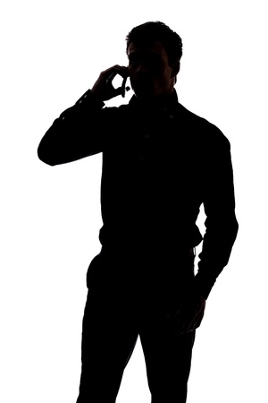 cellphone in hand: Man talking on cell phone in silhouette isolated over white background