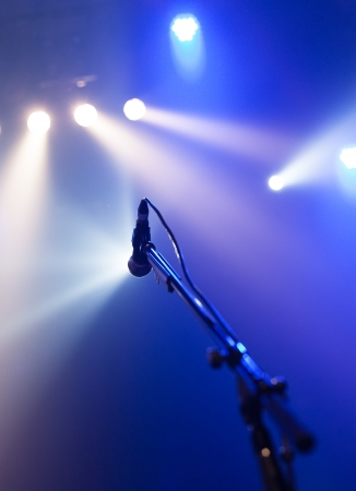 Microphone on empty stage waiting for a voice with copyspace and back light photo