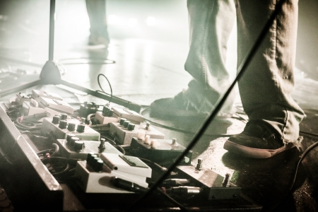 pedals: Guitar Pedals on a Stage with Live Band Performing During a Show. Low light image with copyspace