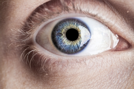 close up image: Macro blue eye with lots of details using studio lights
