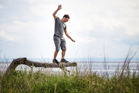 Young Adult Balancing on a dead Tree in Nature in Vacation, just for Fun Stock Photo