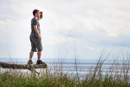 Young Adult in Nature Looking at The View With the Ocean in Background