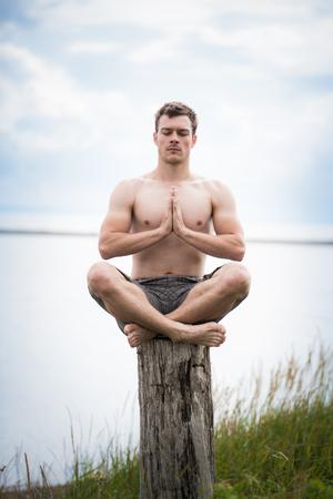 hombres haciendo ejercicio: Adulto joven que hace la Sukhasana (posición Easy) en el Yoga en un tocón en la Naturaleza