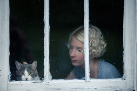 Woman and Cat Looking at the Rainy Weather By the Window Frame