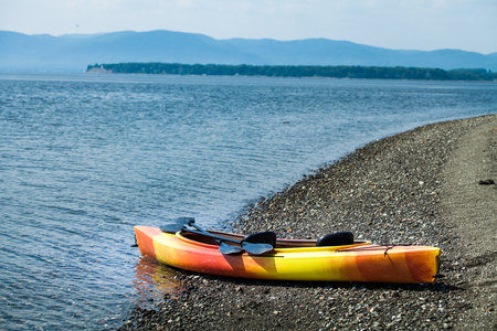 Orange and Yellow Kayak With Oars on the Sea Shore During a\ beautiful Day of Summer