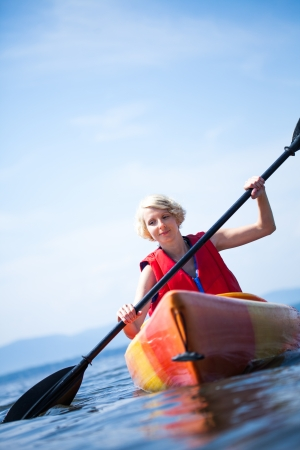 Young Woman Kayaking Alone on a Calm Sea and Wearing a Safety Vest 免版税图像
