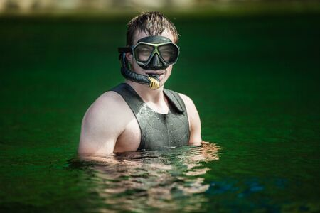 freediving: Funny Young Adult Snorkeling in a river with Goggles and Scuba.