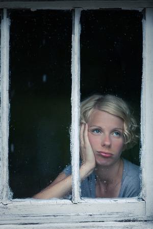 Bored Frau Blick auf das regnerische Wetter Durch die Fensterrahmen Standard-Bild
