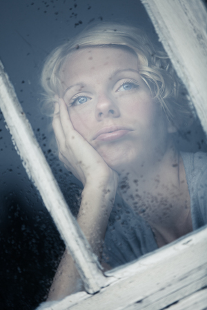 is raining: Bored Woman Looking at the Rainy Weather By the Window Frame Stock Photo