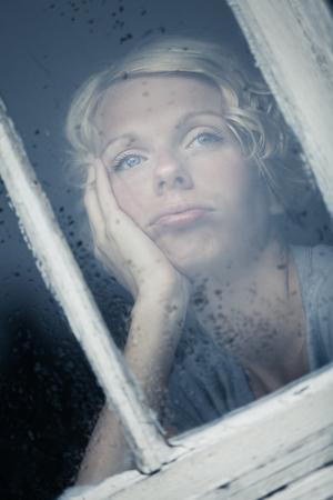 lloviendo: Mujer aburrida Mirando el tiempo lluvioso de marco de la ventana Foto de archivo