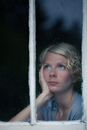 boring frame: Bored Woman Looking at the Rainy Weather By the Window Frame Stock Photo
