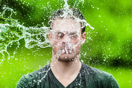 wet men: Young Adult That Got Completely Drenched with Green Background Stock Photo