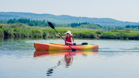 lifejacket: Young Woman Kayaking Alone on a Calm River and Wearing a Safety Vest