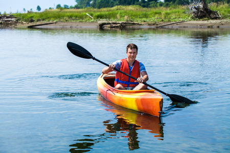 Young Man Kayaking Alone on a Calm River and Wearing a Safety Vest 스톡 콘텐츠
