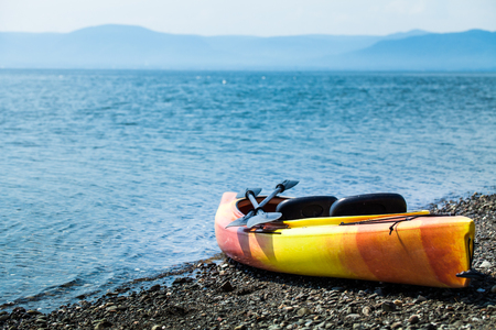 paddling: Orange and Yellow Kayak With Oars on the Sea Shore During a beautiful Day of Summer Stock Photo