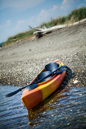 Orange and Yellow Kayak With Oars on the Sea Shore During a beautiful Day of Summer photo