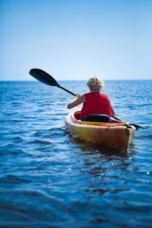 safety vest: Young Woman Wearing a Safety Vest Heading out to sea Alone on Calm Water