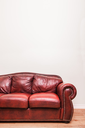 red wall: Luxurious Red Leather Couch in front of a blank wall to ad your text, logo, images, etc. Stock Photo