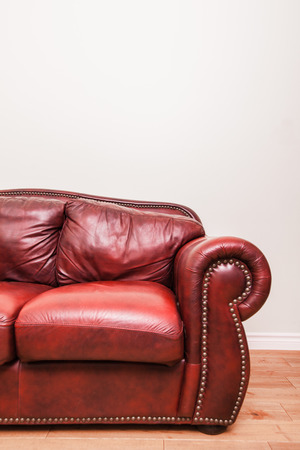 Luxurious Red Leather Couch Detail in front of a blank wall to ad your text, logo, images, etc. photo