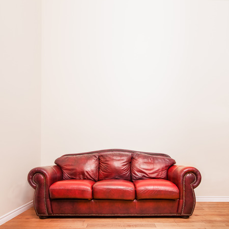 couch: Luxurious Red Leather Couch in front of a blank wall to ad your text, logo, images, etc. Stock Photo