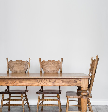 Wooden Dining room table and chair details and blank wall for your text, image or logo. Standard-Bild