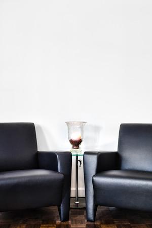 Moderne binnenlandse ruimte en witte muur met ruimte voor uw tekst. Twee luxe bank en glazen tafel met accessoires van uw keuze.