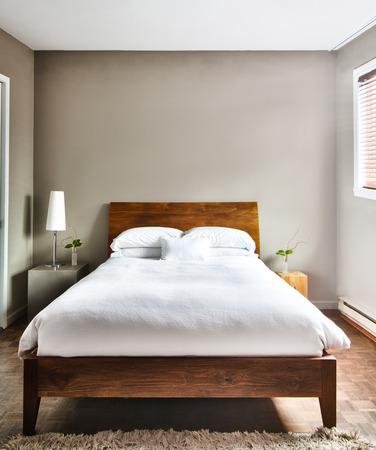 Mooie schone en moderne slaapkamer met een lege muur om wat tekst, logo, afbeelding, etc. toe te voegen