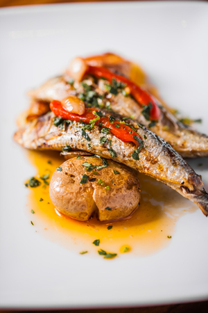 sardinas: A la parrilla Sardinas Placa con pimiento rojo y patata en un restaurante portugués Foto de archivo