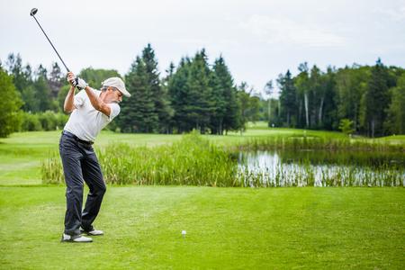 columpios: Golfista maduro en un campo de golf que toma un oscilación en el Start