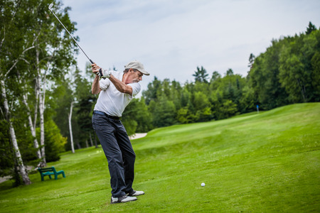Mature Golfer on a Golf Course Taking a Swing on the Start photo