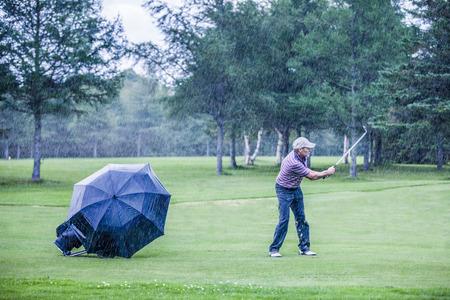 Golfer op een regenachtige dag Swigning in de Fairway (motivatie concept)