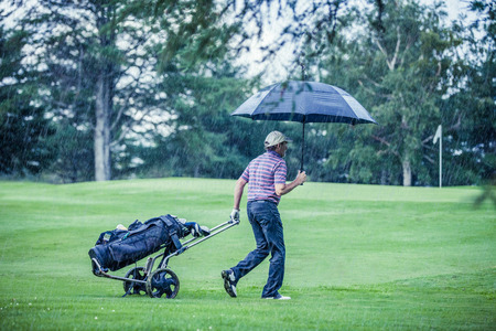 Golfer on a Rainy Day Leaving the Golf Course (the game is annulled because of the storm) 스톡 콘텐츠