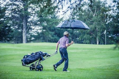 Golfspeler op een regenachtige dag verlaten de Golfbaan (het spel wordt nietig verklaard vanwege de storm)