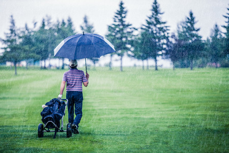 Golfer on a Rainy Day Leaving the Golf Course (the game is annulled because of the storm) Stockfoto
