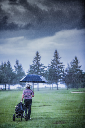 golfers: Golfer on a Rainy Day Leaving the Golf Course (the game is annulled because of the storm) Stock Photo