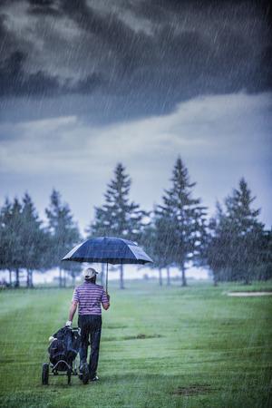 Golfer op een regenachtige dag verlaten van de Golfbaan (het spel wordt nietig verklaard vanwege de storm)