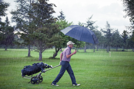 grouchy: Golfer on a Rainy Day Leaving the Golf Course (the game is annulled because of the storm) Stock Photo
