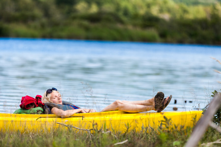overwrought: Tired Woman Sleeping in a Yellow Kayak