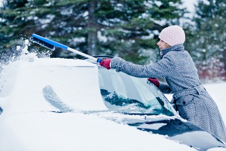 Woman Removing Snow from a Car with a Broom after the Blizzard Stock Photo