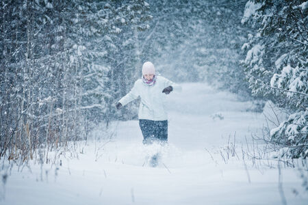 joys: Cheerful Woman Running in Forest and Enjoying the joys of Winter